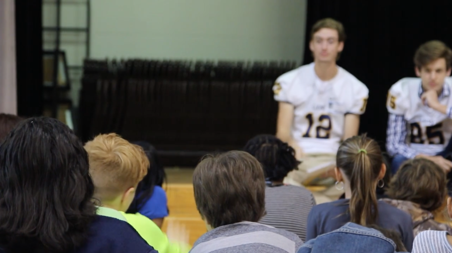 The Lions football team reads to elementary students