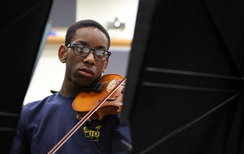 During class junior Josh Snead plays the viola as he reads his sheet music.