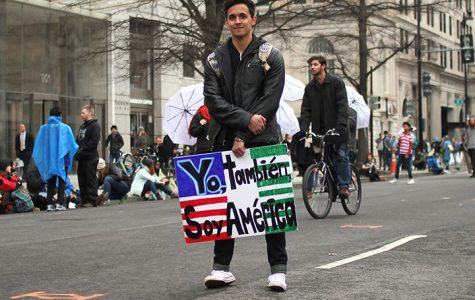 "A young man holds a sign saying ""Yo, tambien, soy American"" which translates to ""I am also American."""