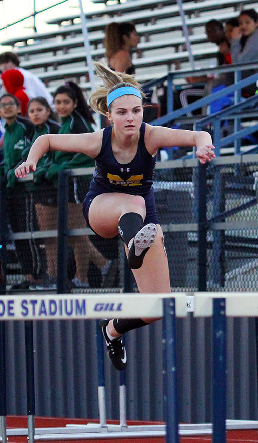 At the district track meet,  sophomore Gigi Gray jumps across a hurdle.