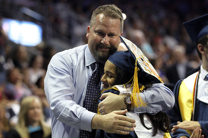 Mr. Michael Bennett hugs graduate Neelam Bohra during his last graduation as assistant principal at MHS.