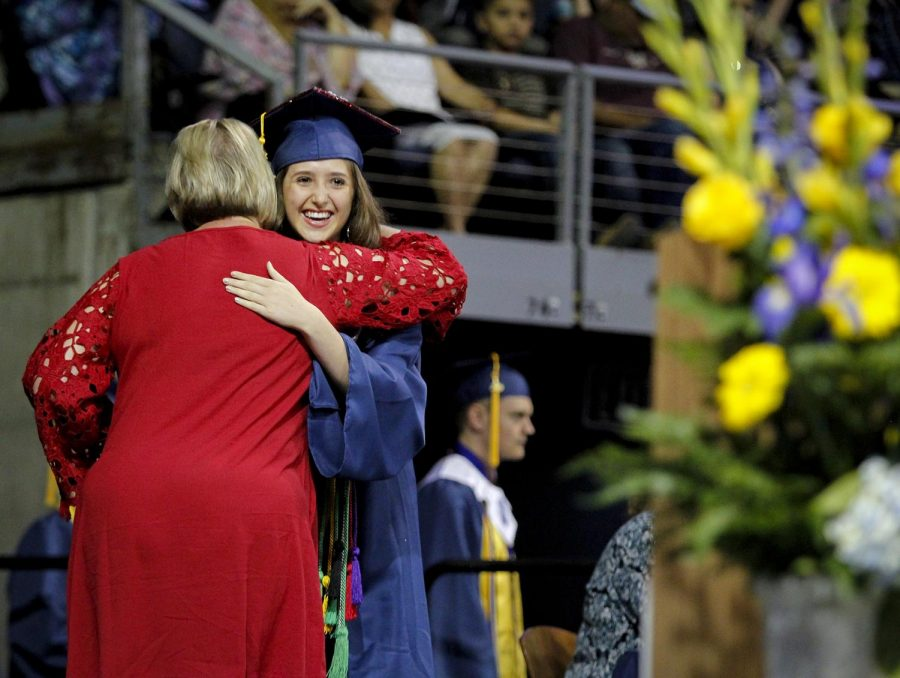 Emory Otto shares a celebratory hug after receiving her diploma.