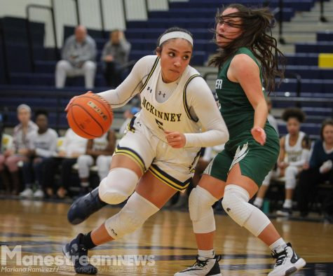 While passing an opposing player, junior Trinity White dribbles the ball down the court.