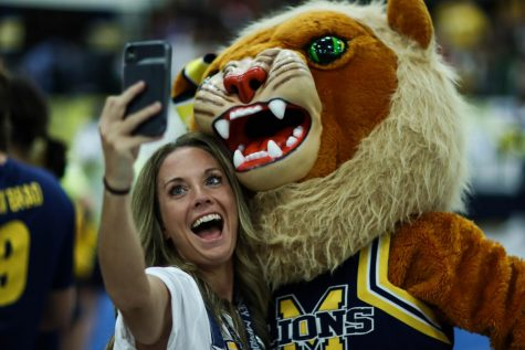During the first pep-rally, Marquette Director Amy Neely takes a selfie with Leah the Lion. (Sydney Allan)