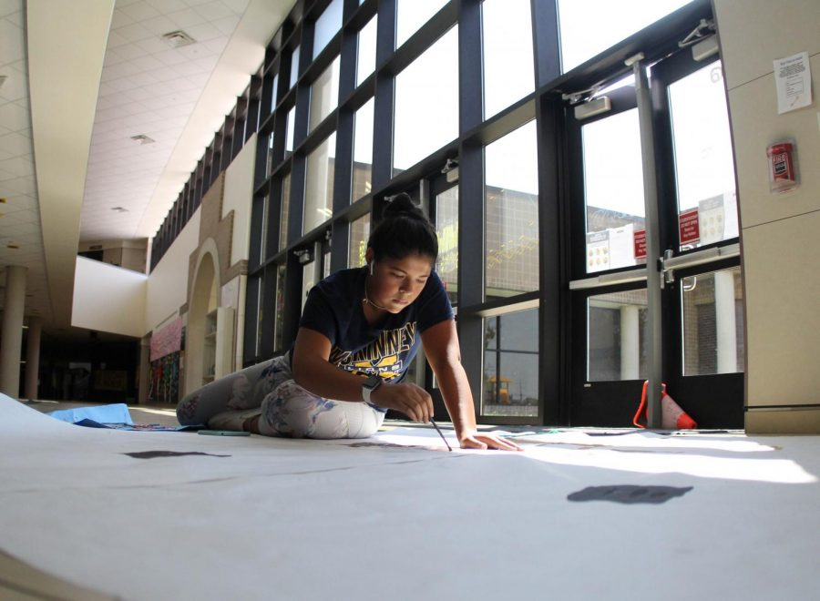 During Dec the Halls for homecoming, Sofia Janah paints a poster for the main hall. (Sage Watz)